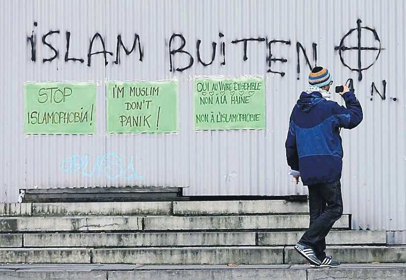 Pasted signs reading ,stop islamophobia, and ,I'm muslim don't panic, are seen under anti-Islam grafitti during a protest against Islamophobia in front of the Brussels' Justice Palace on Oct. 26.