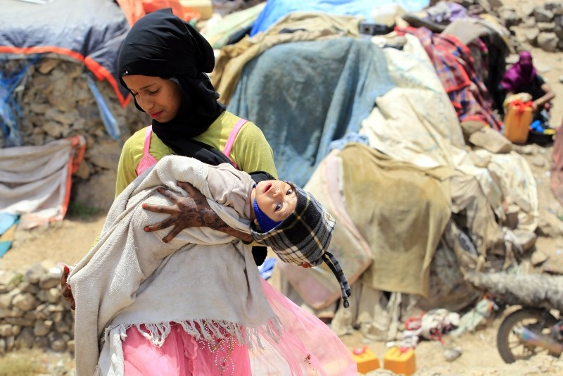 A displaced Yemeni girl holds her infant sister outside temporary shelters at a camp for Internally Displaced Persons (IDPs) on the outskirts of Sana'a, Yemen, 25 August 2018. (EPA Photo)