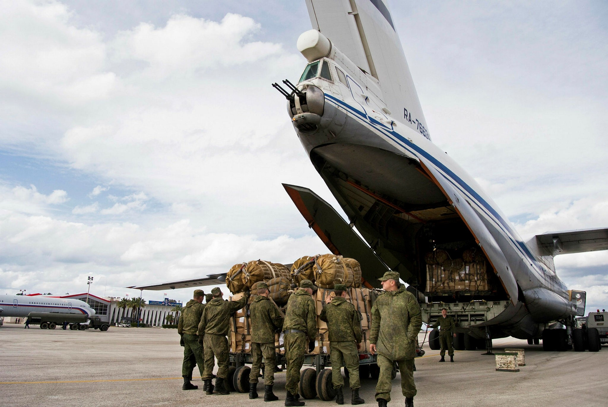 In this Wednesday, Jan. 20, 2016 file photo, Russian air force personnel prepare to load humanitarian cargo on board a Syrian Il-76 plane at Hemeimeem air base in Syria. (AP Photo)