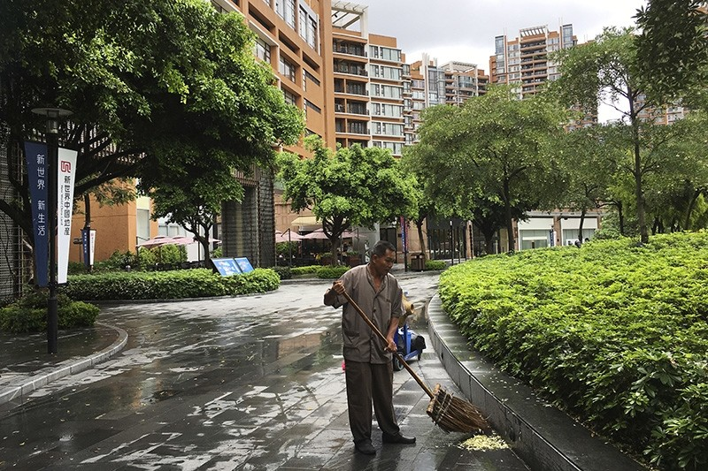 A worker sweeps near the high-rise apartment buildings in the Canton Place where U.S. government workers who experienced unexplained health issues in Guangzhou in south China's Guangdong province, Thursday, June 7, 2018. (AP Photo)
