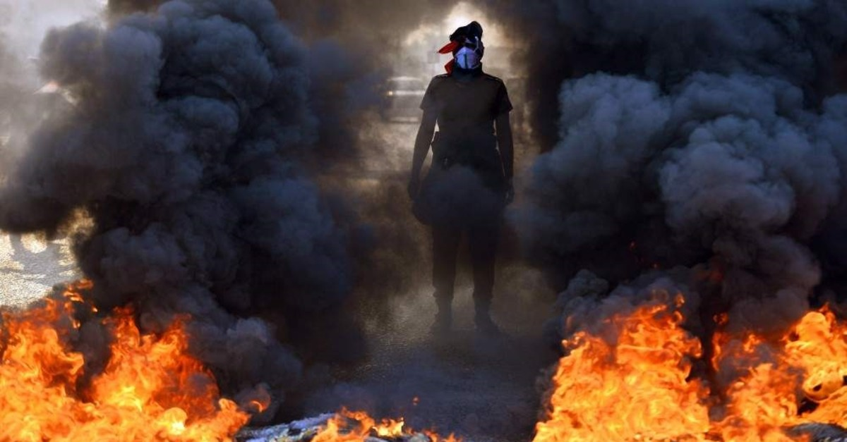A protester stands before burning tires at a roadblock in the holy city of Najaf, Iraq, Nov. 26, 2019. (AFP Photo)
