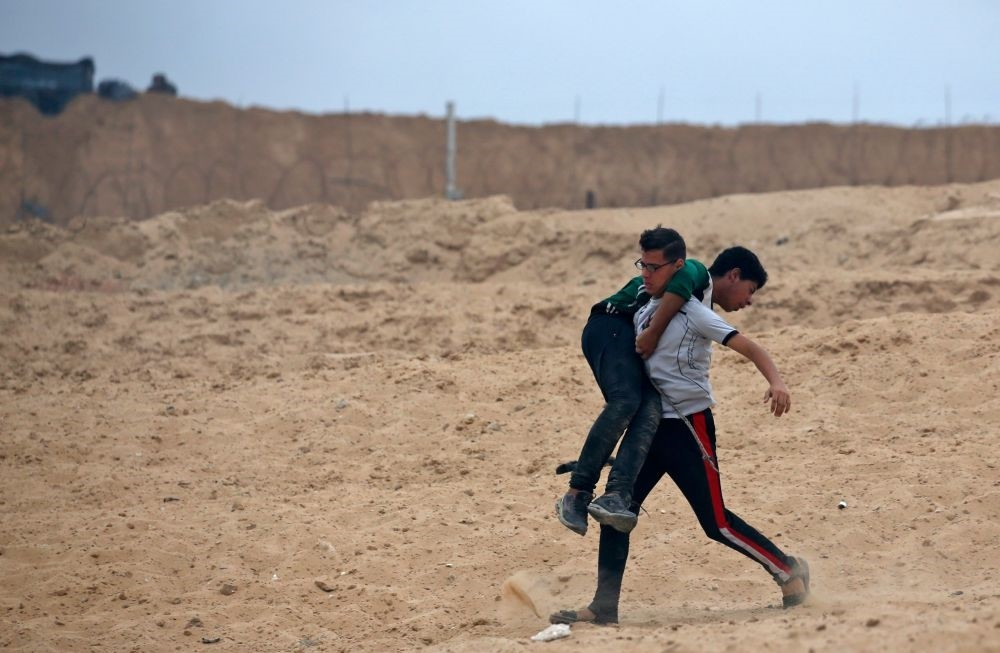 A Palestinian protestor carries a young boy who was injured during a demonstration on a beach near the maritime border with Israel in the northern Gaza Strip, Oct. 1.