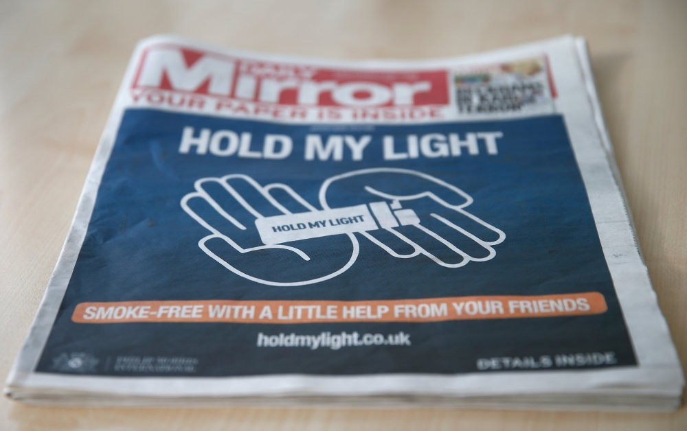 The front of a four page wraparound advertisement by Philip Morris calling on people to quit smoking for 30 days is seen on the front page of the daily Mirror in London, Oct. 22.