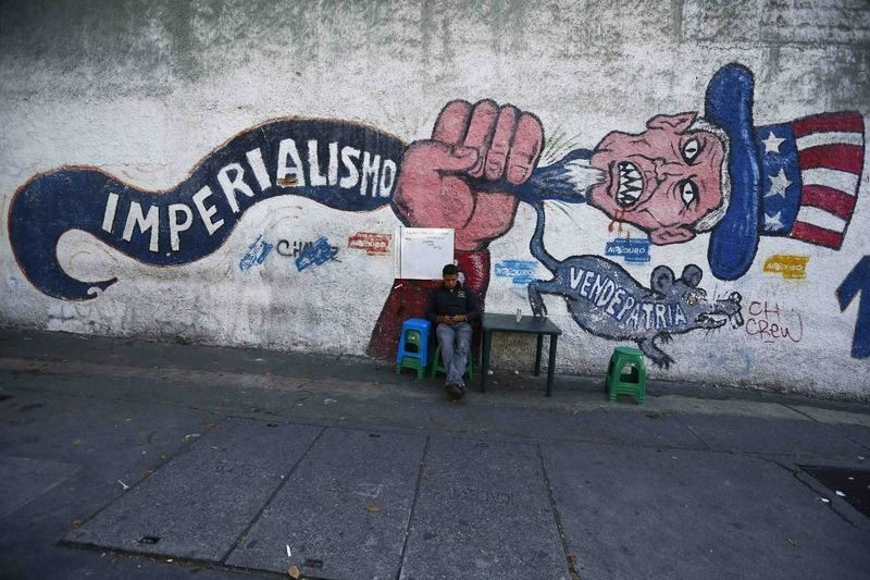 A man sits next to graffiti, which reads ,imperialism, and ,vendepatria, (traitor), referring to the U.S., Caracas, Venezuela, March 9, 2015.