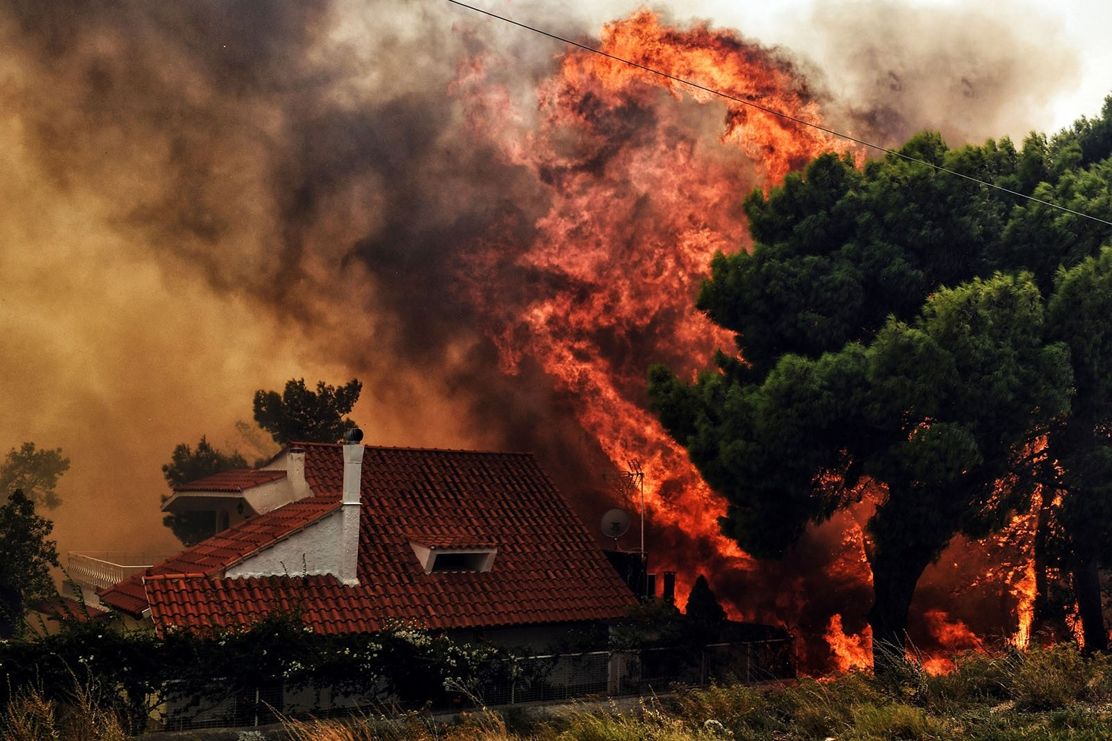 A house is threatened by a huge blaze during a wildfire in Kineta, near Athens, on July 23, 2018.