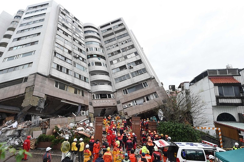 Rescuers (C) working on the recovery of a body rush out during an aftershock from a building leaning at a precarious angle in Hualien on February 8, 2018 after the city was hit by a 6.4-magnitude quake late on February 6. (AFP Photo)