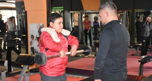 Muhammad (L) works out with an instructor at the gym.