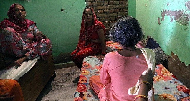 Shri Devi, the 49 years old victim whose braids chopped off allegedly by unknown person, sits with her back to the camera inside her house  in Kanganheri village, the outskirts of Delhi, India, 01 August 2017 EPA Photo