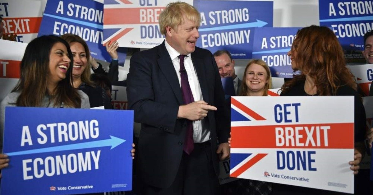 Britain's Prime Minister Boris Johnson (center) speaks to activists and supporters as he poses for a photograph at the Conservative Campaign Headquarters Call Centre, while on the General Election trail, London, Dec. 8, 2019. AP