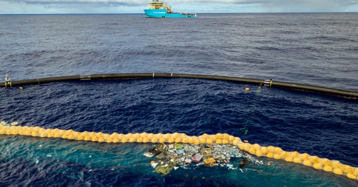 In this undated handout photo provided by The Ocean Clean Up, plastic is retained in front of an extended cork line in the Pacific Ocean (AP Photo)
