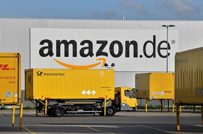 In this file photo dated Wednesday, Nov. 14, 2018, post trucks leaves the Amazon Logistic Center in Rheinberg, Germany. (AP Photo)
