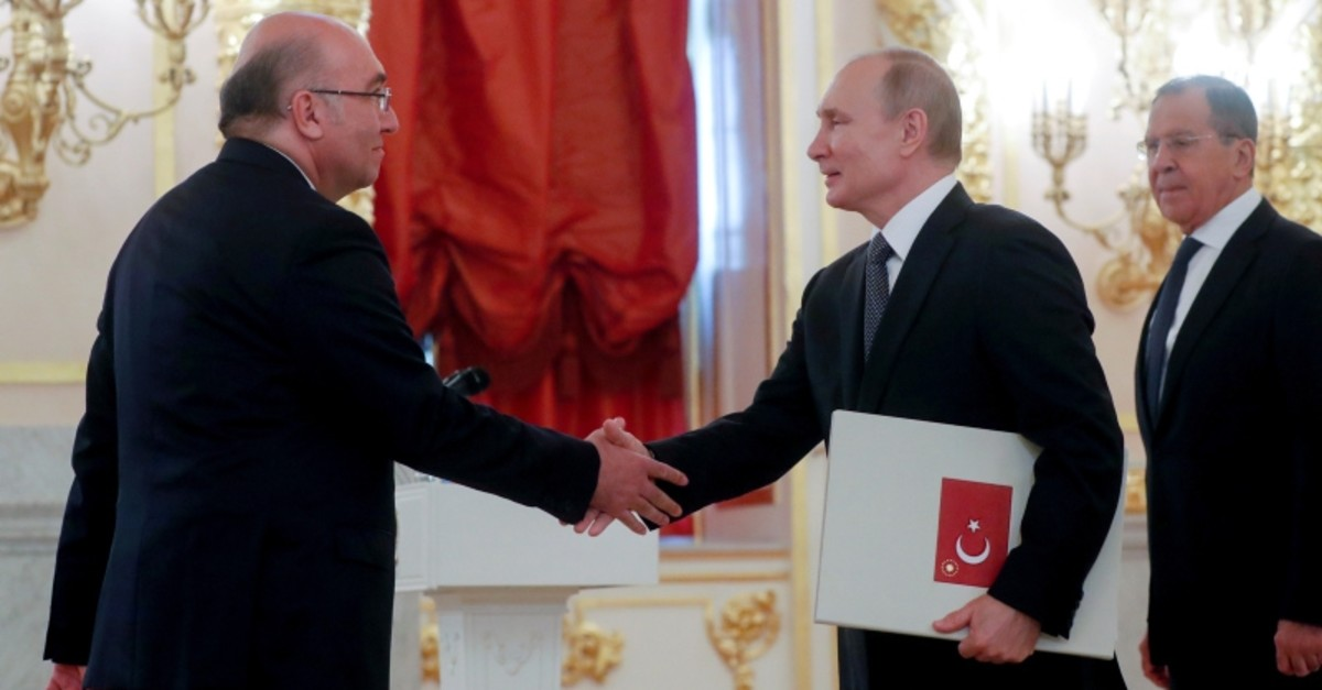 Russian President Vladimir Putin shakes hands with Turkish ambassador Mehmet Samsar as FM Sergey Lavrov looks on, during a ceremony at the Alexander Hall of the Grand Kremlin Palace in Moscow, Russia, July 3, 2019. (Maxim Shipenkov/Pool via Reuters)