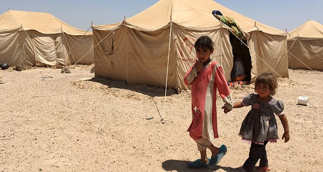 Displaced Iraqi children stand outside a tent at a newly-opened camp in the government-held town of Amriyat al-Fallujah 50 kilometres (30 miles) southwest of Baghdad, on May 29, 2016 (AFP Photo)