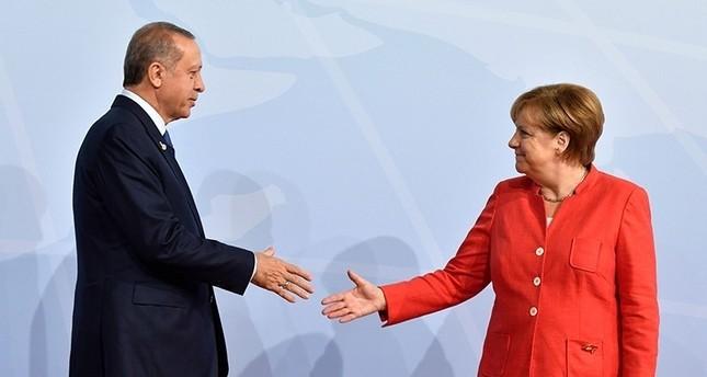 أردوغان يصافح ميركل قبل بدء اجتماعات مجموعة العشرين G20  في مدينة هامبرغ شمالي ألمانيا يوليو 2017 (وكالة الأنباء الفرنسية)