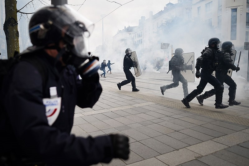 Riot police charge demonstrators during clashes on the side lines of a nation-wide action day of French civil servants against French government's string of reforms on March 22, 2018  in Nantes, western France. (AFP Photo)