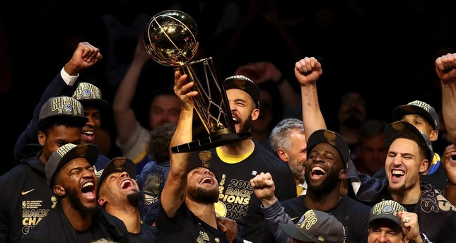 The Golden State Warriors celebrate with the Larry O'Brien Trophy after defeating the Cleveland Cavaliers in Game 4 of the 2018 NBA Finals at Quicken Loans Arena  June 8 in Cleveland.