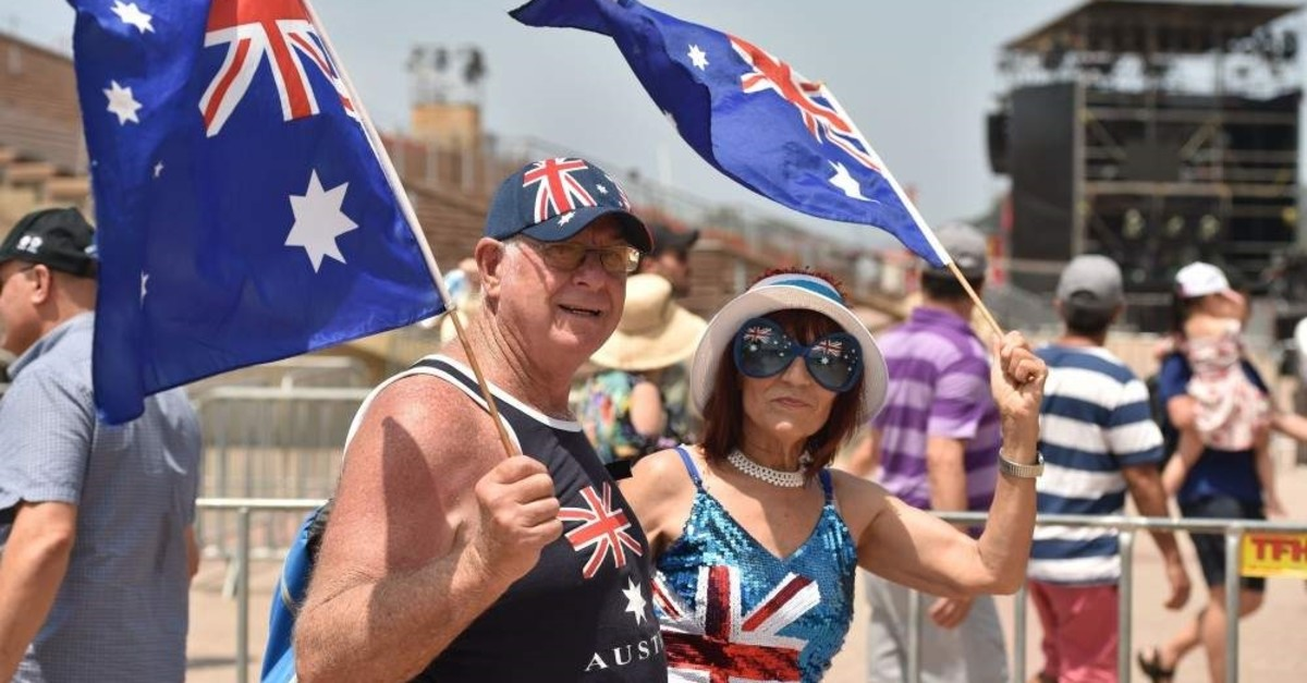 People wave the country's flag to celebrate Australia Day in Sydney on Jan. 26. (Photo by PETER PARKS / AFP)