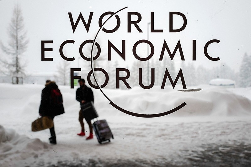 Two people leave the Congress Centre under snow ahead of the opening of the World Economic Forum (WEF) 2018 annual meeting, on Jan. 22, 2018, in Davos, eastern Switzerland. (AFP Photo)