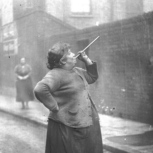 A woman blowing a whistle to wake people up in the morning.