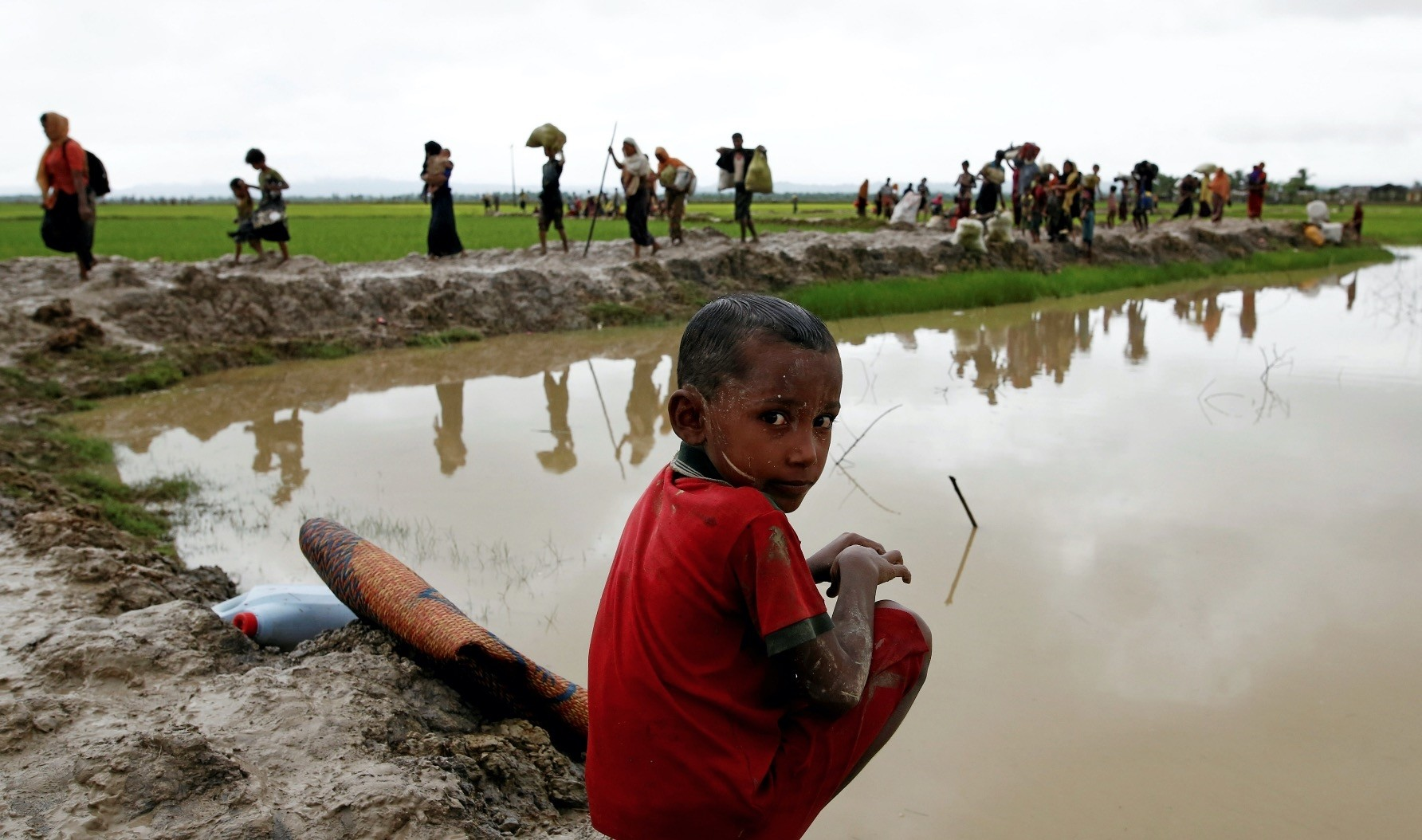 A Rohingya refugee boy reacts to the camera as he sits in mud after travelling over the Bangladesh-Myanmar border in Teknaf, Bangladesh, Sept. 1.
