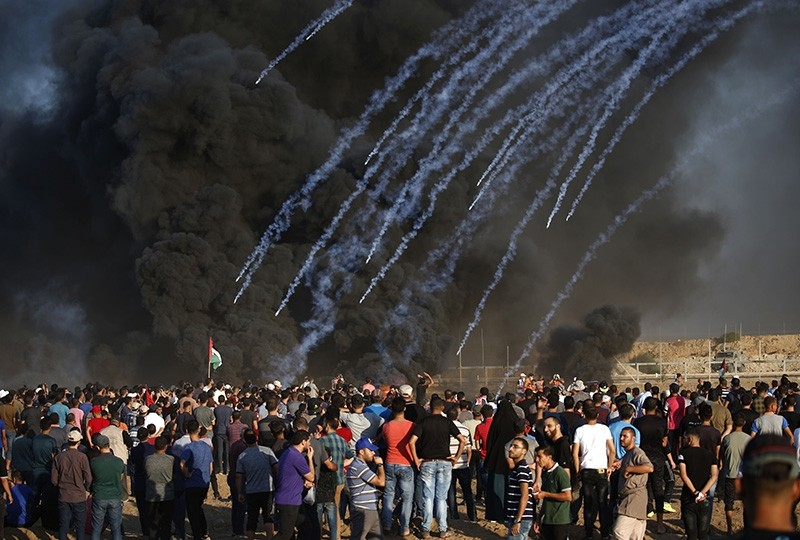 Palestinian protesters watch as tear gas canisters fired by Israeli forces land through black smoke of burning tires during a demonstration along the Israeli fence east of Gaza City on Sept. 14, 2018. (AFP Photo)