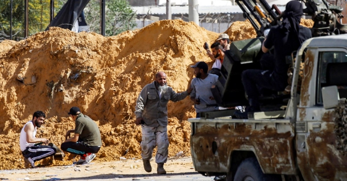 This picture taken on April 10, 2019 from the side of forces loyal to Libya's Government of National Accord (GNA) shows a view of fighters taking cover behind a dirt barrier during clashes south of capital Tripoli's suburb of Ain Zara. (AFP Photo)