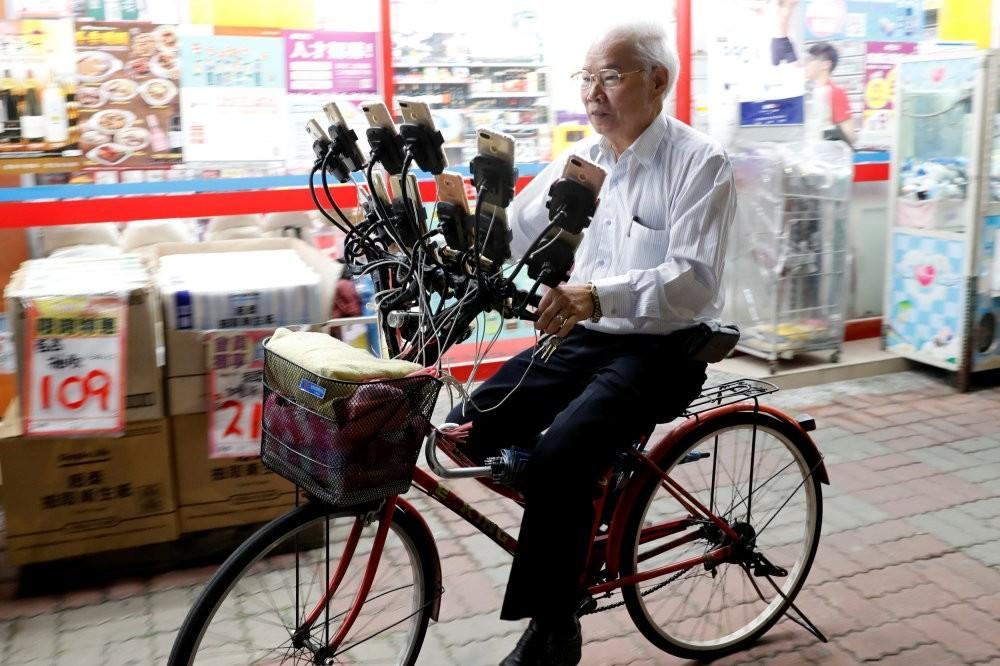 Taiwanese Chen San-yuan, 70, known as ,Pokemon grandpa,, rides his bicycle while playing ,Pokemon Go, on 15 mobile phones, New Taipei City, Taiwan, Nov. 12.