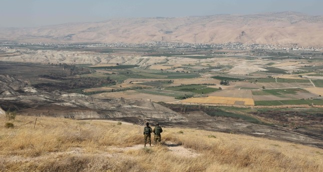 In this file photo taken on June 23, 2019 Israeli soldiers stand guard in an old army outpost overlooking the Jordan Valley  between the Israeli city of Beit Shean and the West Bank city of Jericho (AFP Photo)