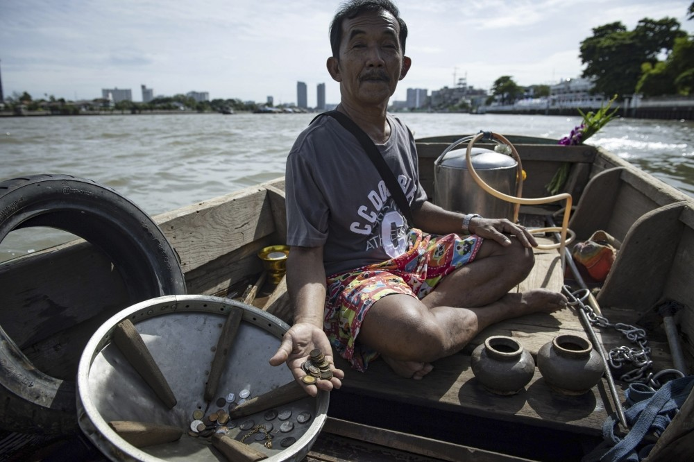 Bhoomin Samang holding rare coins he found during previous diving trips to the bottom of the Bangkok's Chao Phraya river.