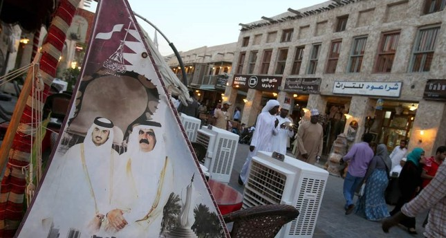 This file photo taken on June 25, 2014 shows people walking past a banner bearing portraits of former emir of Qatar Sheikh Hamad bin Khalifa al-Thani (R) and his son current leader Sheikh Tamim bin Hamad al-Thani displayed at Souq Waqif in Doha.