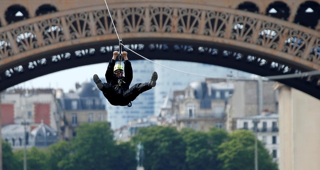 A participant rides a zip line from the 2nd floor of the Eiffel Tower, 115 metres above the ground along an 800-metre long route, as part of a free event operating until June 11 in Paris, June 4, 2017. (AFP Photo)