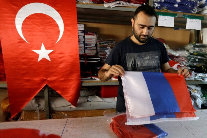 An employee of a flag-making factory folds a Russian flag as a Turkish flag adorns the display at left, in Istanbul, Tuesday, Aug. 9, 2016. (AP Photo)