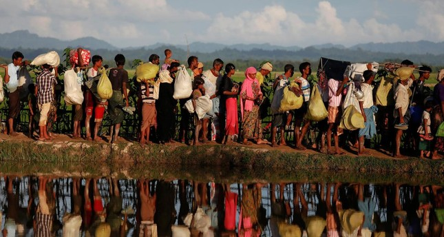 Rohingya refugees who fled Myanmar wait to be let through by Bangladeshi border guards after crossing the border in Palang Khali, Bangladesh, Oct. 9, 2017.