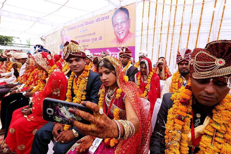 An Indian bride takes a selfie with her husband during a mass marriage ceremony on the occasion of the Akshaya Tritiya festival  Bhopal, India, 29 April 2017 (EPA Photo)