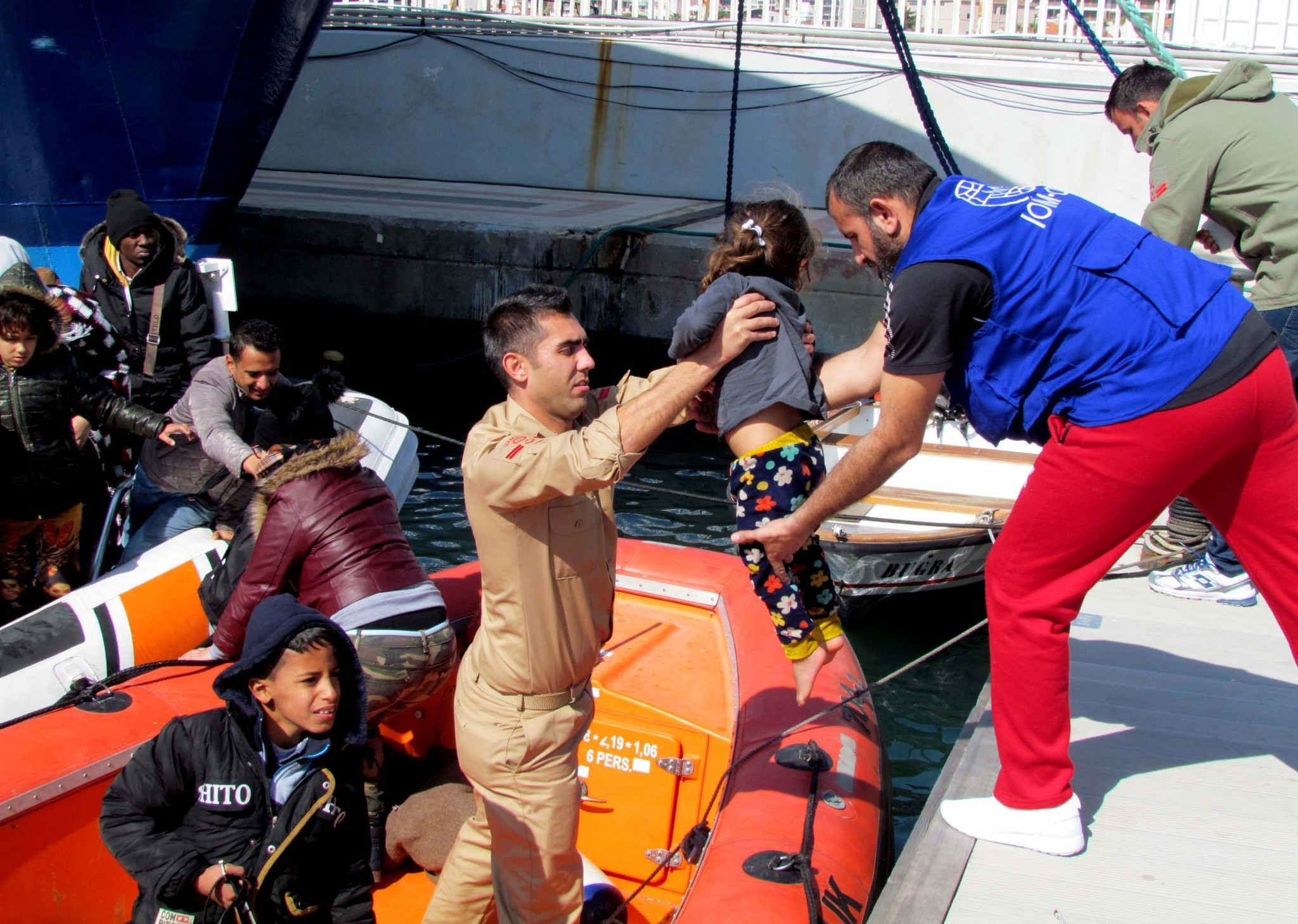 Coast Guard officers help migrants caught Sunday en route to Chios island of Greece to the shore.
