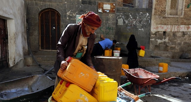 Yemenis fill jerry cans with drinking water from a donated source amid widespread disruption of water supplies in Sanaa, Dec. 9.