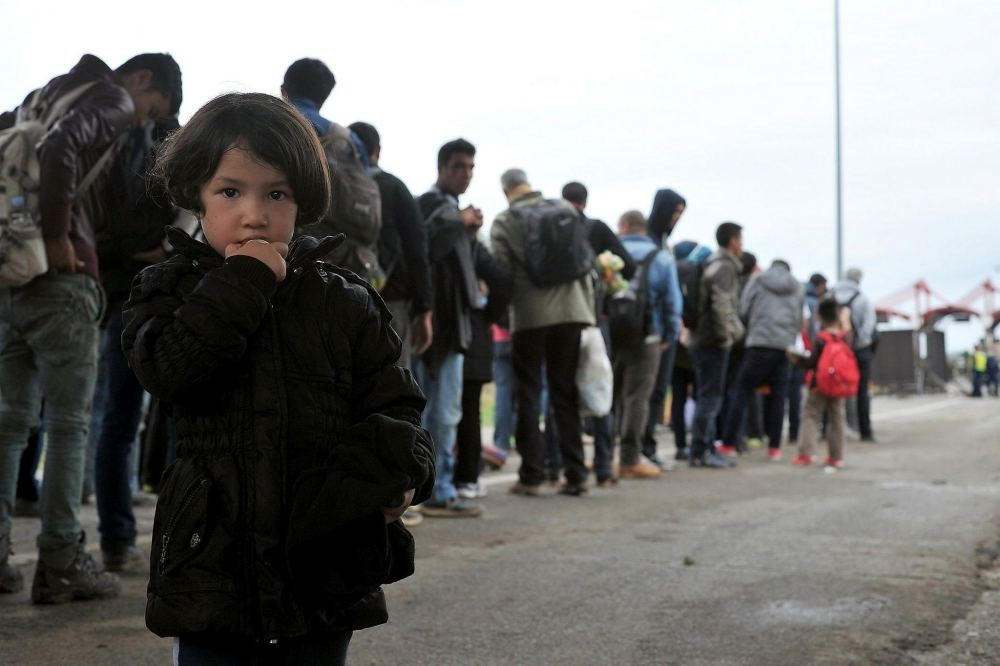 A migrant girl together with a group of Middle Eastern migrants wait to cross the Hungarian-Croatian border.