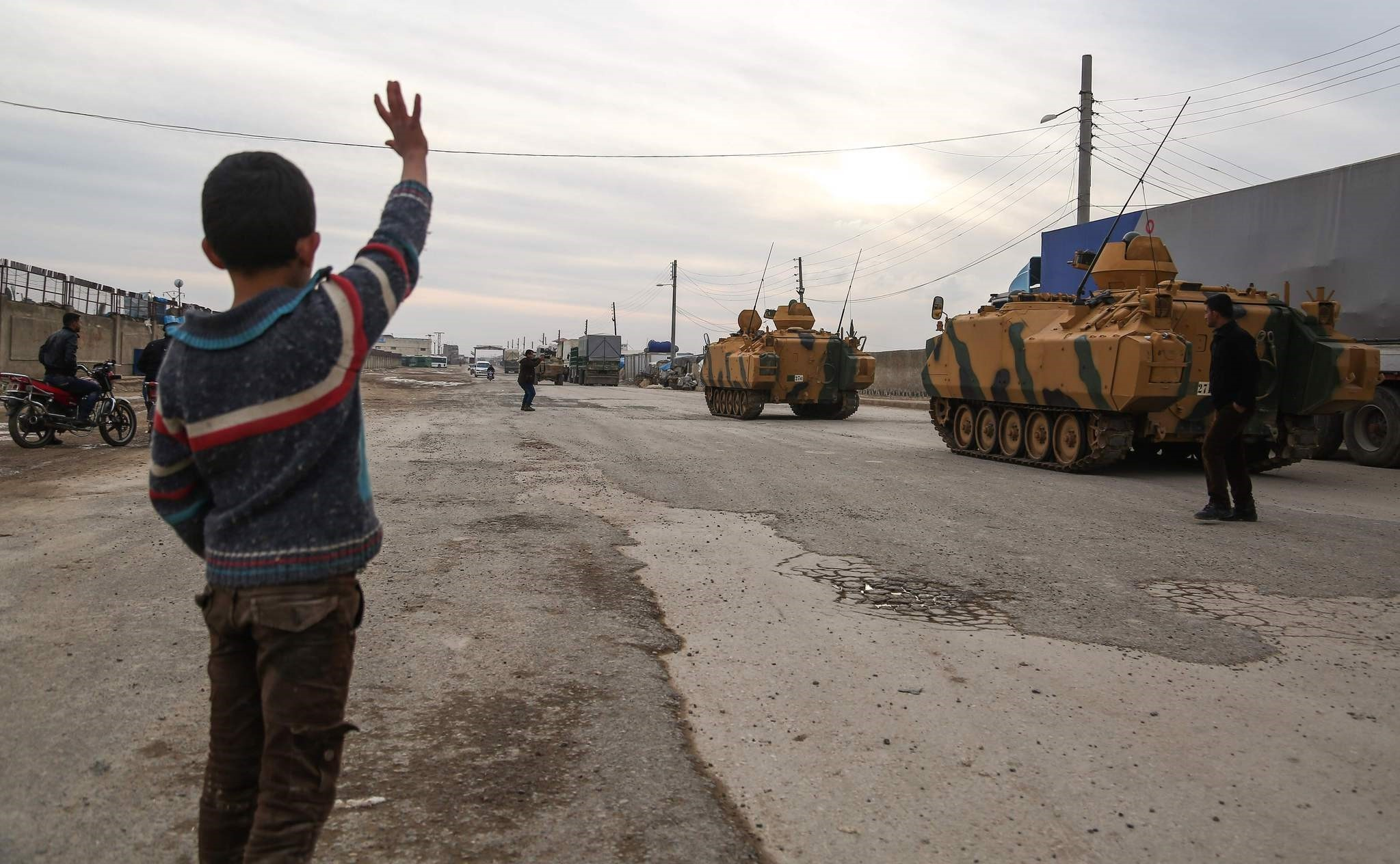 A boy waves at Turkish armoured vehicles passing through the Bab al-Salamah border crossing between Turkey and Syira, Jan. 21.