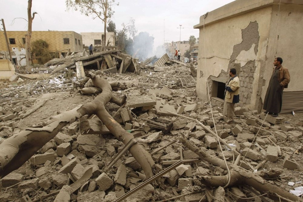 Men standing on rubble as they inspect a site hit by what activists say was a Scud missile from forces loyal to the Assad regime, Raqqa, eastern Syria, Nov. 29, 2013.