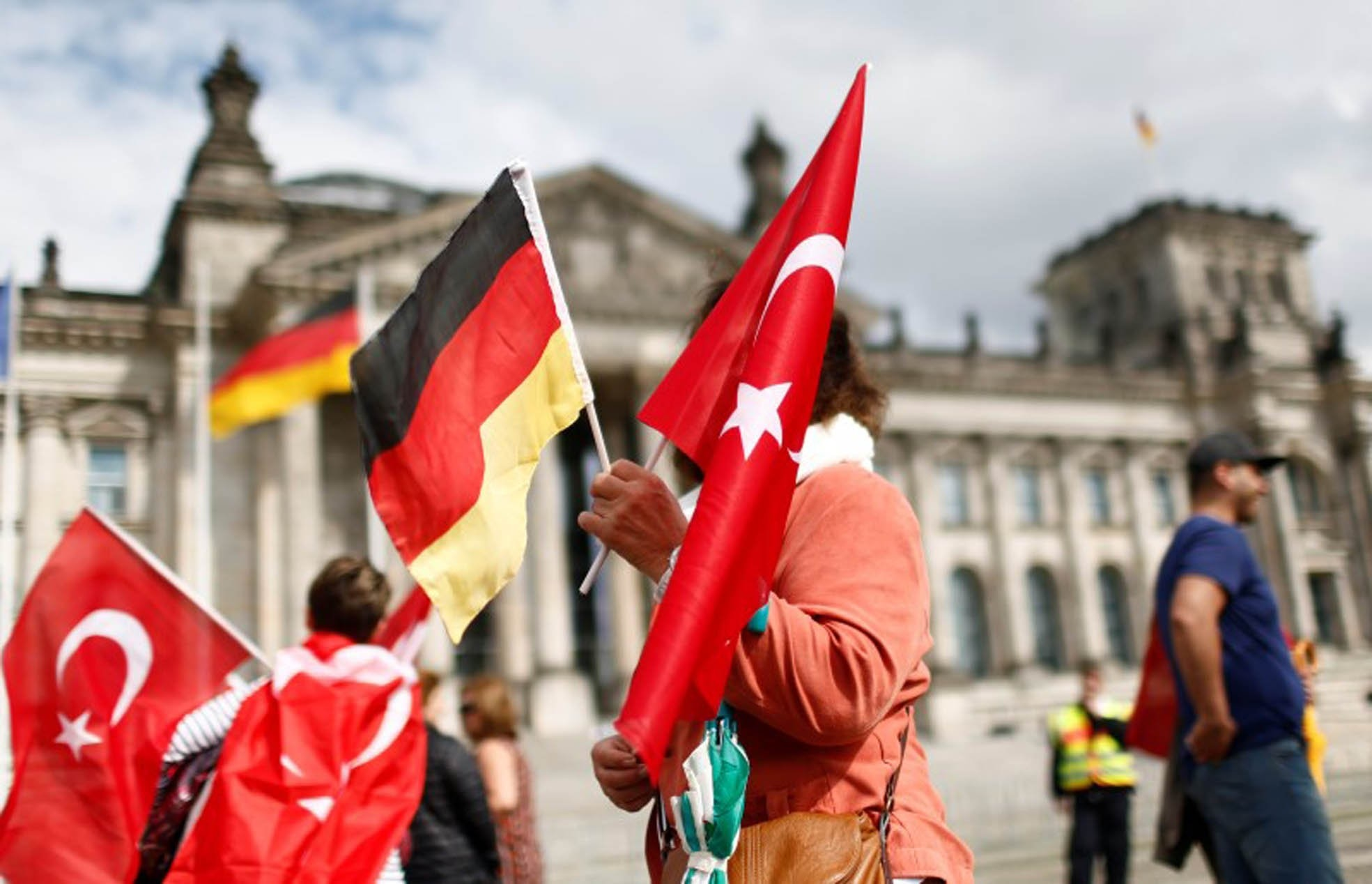 A woman holds Turkish and German flags in front of the Reichstag building, which houses the German Parliament, Berlin, June 1, 2016.