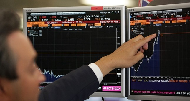 A trader from ETX Capital points to a Bloomberg terminal showing the FTSE 100 index following a speech by Finance minister George Osborne in central london on June 24, 2015 (AFP Photo)