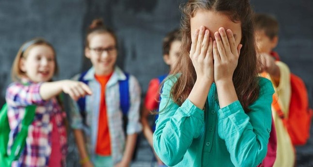 Schoolgirl crying on background of classmates teasing her. iStock