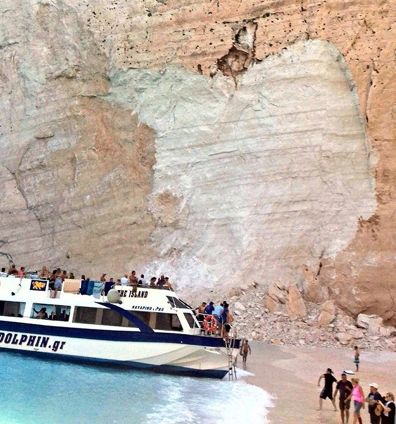 People embark a vessel after a landslide occurred at the popular beach of Navagio, or Shipwreck Beach, on the western island of Zakynthos, Greece, Thursday, Sept. 13, 2018. (AP Photo)