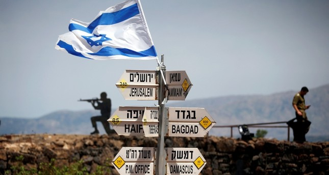 Israeli soldier stands next to signs pointing out distances to different cities, on Mount Bental, an observation post in the Israeli-occupied Golan Heights that overlooks the Syrian side of the Quneitra crossing, Israel May 10, 2018. (Reuters Photo)