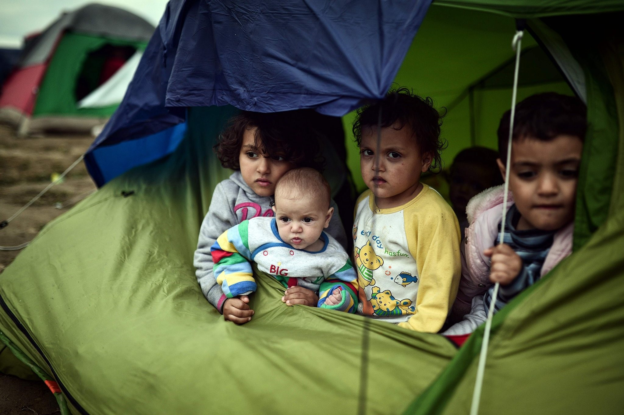 Migrant children stranded in Greece struggle to survive with other a tent for shelter. (AFP Photo)