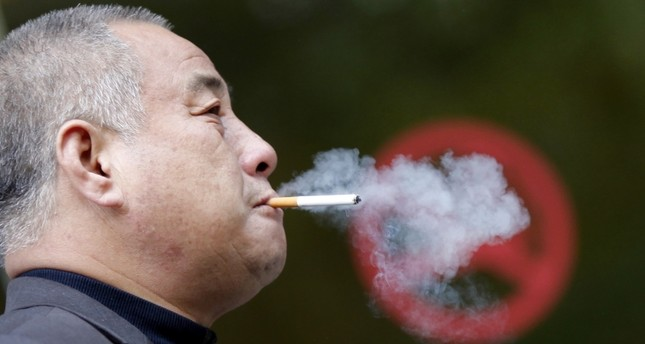 A man smokes next to a No Smoking sign in downtown Shanghai. (REUTERS Photo)