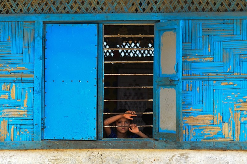A Rohingya refugee looks out from a school window at Kutupalong refugee camp in Bangladesh's Ukhia district on April 5, 2018. (AFP Photo)