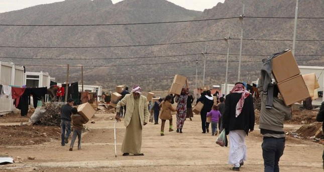 Displaced Iraqi people from the minority Yazidi sect, fleeing violence in the Iraqi town of Sinjar west of Mosul, walk to the Qadia camp on the outskirts of Dohuk province, Dec. 7, 2014.