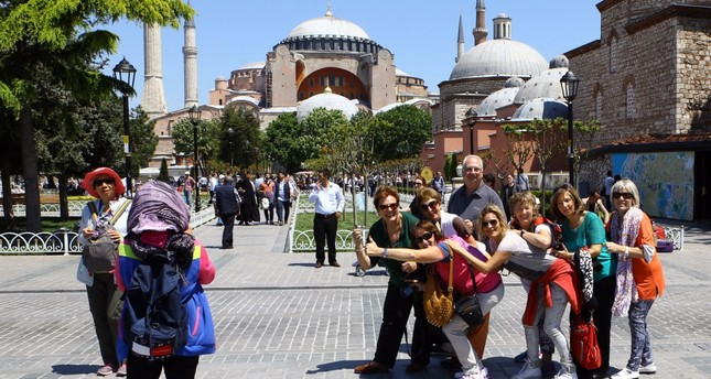 Tourists pose for photos in front of Hagia Sophia, Istanbul.