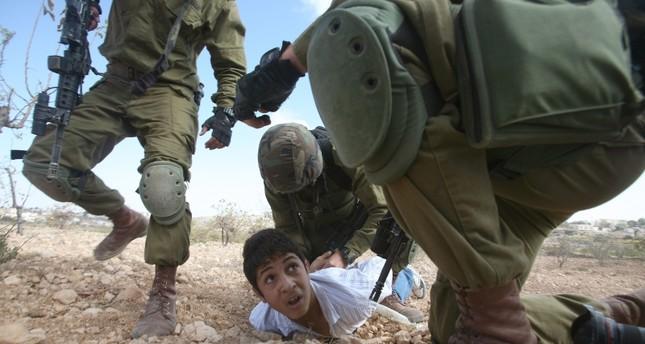 أرشيفية- جنود إسرائيليون يعتدون على طفل فلسطيني لإلقائه الحجارة خلال احتجاجات بالضفة (وكالة الأنباء الفرنسية)